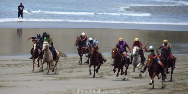 Spectator in the surf at Kaiaua Beach Horse Races