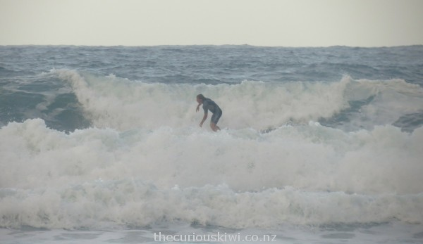 Surfing the fierce waves at Hot Water Beach