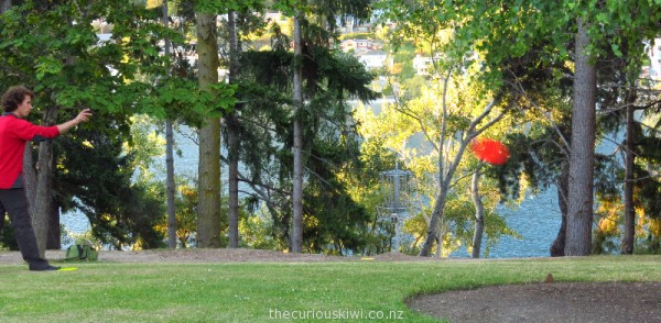Queenstown disc golf - red disc on its way to the chain basket